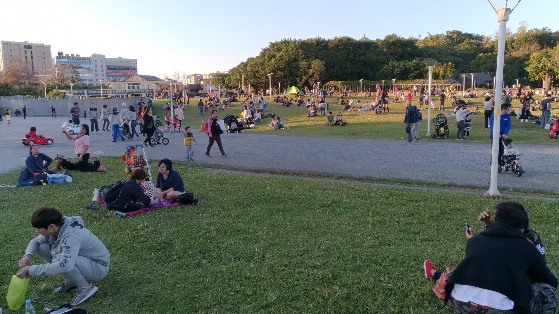Adults are chatting and children are running on the lawn in the Yuanshan Area of Taipei Expo Park.